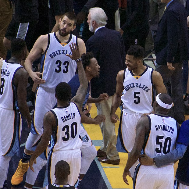 With the 110-108 OT victory in the record books, Marc Gasol, who hit the game-winner, celebrates with his Griz teammates as Spurs Head Coach Gregg Popovich exits the FedExForum court. (Photo: Karanja A. Ajanaku)