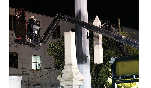 A monument to a deadly white supremacist uprising in 1874 was removed under cover of darkness by workers in masks ...