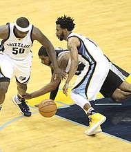 As Zach Randolph of the Grizzlies goes for the ball, Spurs forward LaMarcus Aldridge scrambles to slow him down.