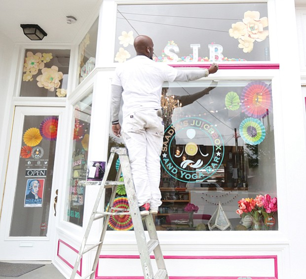Senon Davis brightens the front of Saadia's Juice Box and Yoga Bar, one of the newest businesses in Jackson Ward. Mr. Davis spent a recent Sunday adding fresh, attention-grabbing color to the business at 402½ N. 2nd St. Opened in January, owner Saadia Yasmin combines yoga and belly dancing classes with a mix of Persian-style baked goods, salads and beverages — ranging from coffee, espresso and tea to raw juices and special concoctions of fruit, vegetables and spice smoothies.