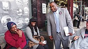 City Councilor Tito Jackson chats with commuters at the Dudley Square bus station as he collects signatures for his mayoral bid.