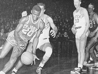Solly Walker dribbles around the defense in this St. John's University photo. He was the first African-American player on the team, joining the varsity squad in 1951 after a year on the freshman team.