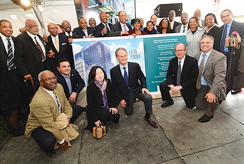 Investors, politicians, community organizers and project team members gather around the unveiled view of the proposed hotel to be built across from the downtown Boston Convention and Exhibition Center. The project, in part, has been to create a new model of unprecedented representation by minority- and women-owned businesses, infusing the Boston economy with a new business diversity. Gov. Charlie Baker, Lt. Gov. Karyn Polito, Mayor Marty Walsh and Massport CEO Tom Glynn also joined in the celebration of the $550 million, 1000-room hotel.
