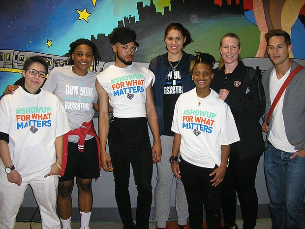 Liberty players Shavonte Zellous and Amanda Zahui B and assistant coach Katie Smith with volunteers and staff at the Ali Forney Center in Harlem