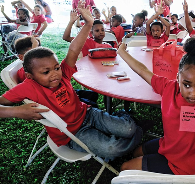 Pick me! // Ahmad Anderson, left, and his Carver Elementary School classmate Zay'Mya Harris wave their hands with the answer during an activity at the Children's Book Festival last Friday at Abner Clay Park in Jackson Ward. The first-graders were among students from four area school systems to participate. Please see more photos, B2.
