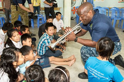 Musician 1st Class Vince Moody, from Severn, Maryland, of the U.S. 7th Fleet Band, Far East Edition, plays trumpet with ...