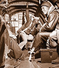 The elite all-black paratrooper unit 'The Triple Nickles' on a training flight aboard their C-47 aircraft.