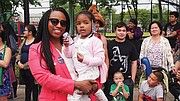 At-large City Councilor Ayanna Pressley enjoys a moment with Alaysha Balkishun (2) during the Dorchester Day parade.