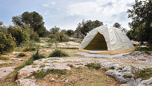 On a hilltop overlooking the Acropolis in Athens, Greece, a tent stands in a clearing among olive trees. Its folds ...