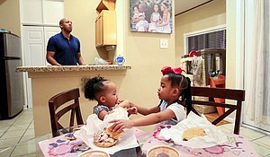 Alex Hicks pauses for a moment as his daughter Alyssa, 5, right, feeds her sister, Alana, 1, during dinner at their home in Houston, Jan. 19. His wife, Marlene Dominguez-Hicks, died of a rare heart disease, peripartum cardiomyopathy, while pregnant with their third child. PPCM is an uncommon form of heart failure during the last month of pregnancy or up to five months after giving birth, according to the American Heart Association.