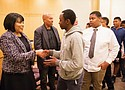 Multnomah County Commissioner Loretta Smith and Los Angeles-based filmmaker A.J. Ali shake the hands of young members of the community attending a town hall to discuss solutions and best practices to address racial disparities in the county's justice system.