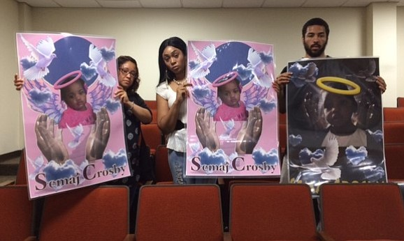Mireya Reyes, Latoya Robinson and Dontraven Perkins held up posters of slain Joliet toddler Semaj Crosby during Will County's June meeting.