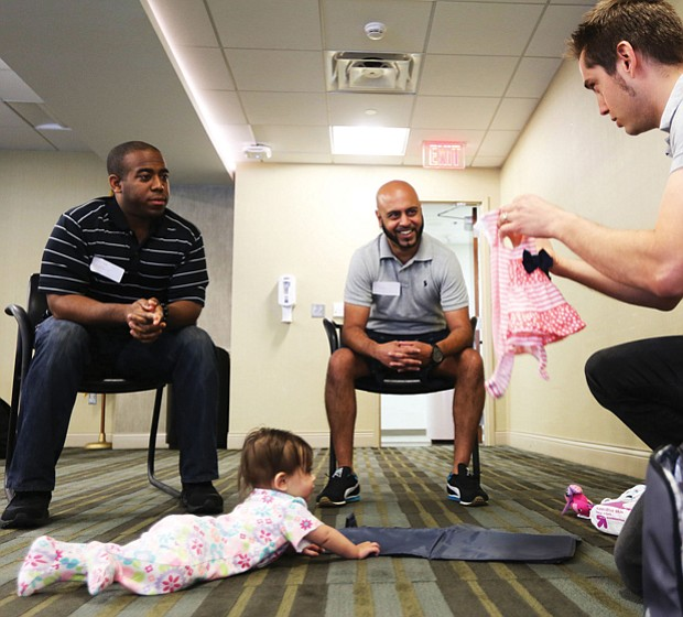 Jeff Duresky of Midlothan, right, shows off the outfit he will put on his daughter Sansa, 7 months, to dads-to-be Jarrod Loadholt, left, of Washington and Ricky Patel of Glen Allen.