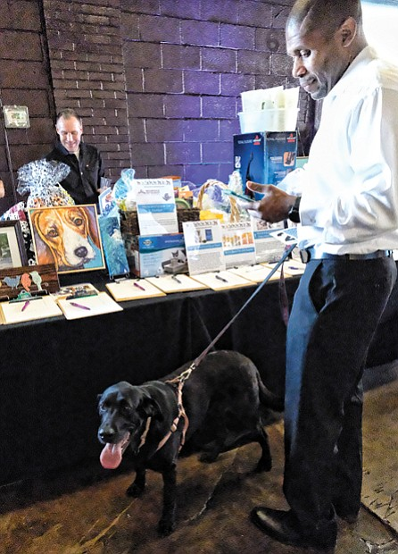 Pet Benefit // Kevin Epps peruses the silent action offerings with his black Labrador, Noell.