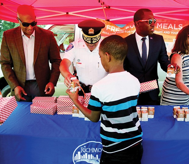 "Jason Marshall, 9, receives a carton of milk and a boxed lunch from Richmond Police Chief Alfred Durham on Monday at the launch of the ""No Kid Hungry Virginia"" summer meals program. Location: The city's new Southside Community Center at 6255 Old Warwick Road. Other officials serving meals include, from left: Richmond City Councilman Michael J. Jones, Mayor Levar M. Stoney, Virginia's First Lady Dorothy McAuliffe and Richmond Delegate Betsy B. Carr. Anyone 18 and under is eligible for free breakfast and lunch through the U.S. Department of Agriculture-supported program without application or registration. Meals are available at 84 sites in Richmond, ranging from city recreation centers, schools and public housing offices to churches and day care centers. The goal is to ensure children receive nutritious meals when school is not in session. In past years, only 35 percent of city youths who receive free meals at school took advantage of the summer program. Mobile phones are making it simpler to find locations. Text the word FOOD or COMIDA to 877-877 and then enter a ZIP code to get information on nearby sites and times of service. Locations also are listed at www.fns.usda.gov/summerfoodrocks."