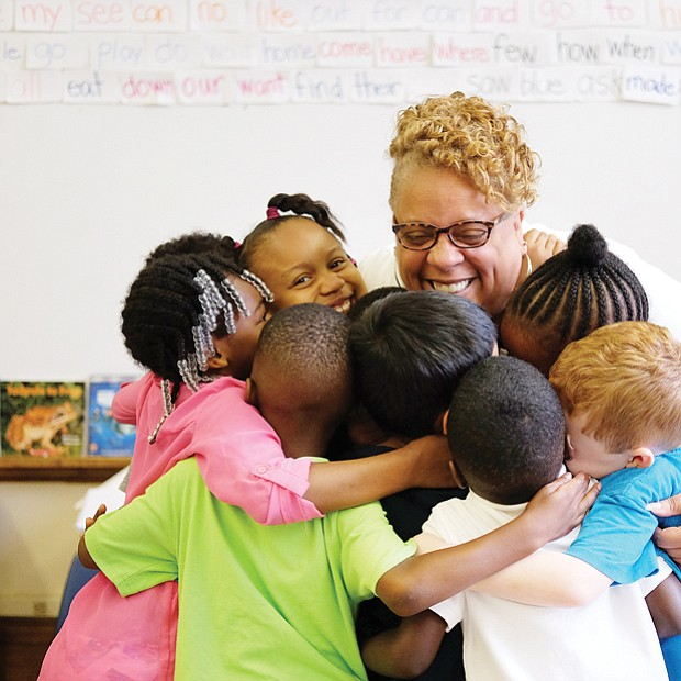 "A hug to last through summer // Richmond's J.E.B. Stewart Elementary School Principal Jennifer Moore gives kindergartners a big group hug last Friday, the last day of school. She reminded students to keep in mind her motto during the summer break: ""Read, read, read."" During the summer, many students forget some of what they have learned during the school year. Called the ""summer slide,"" research indicates that reading just six books during the summer can help prevent loss of progress in reading."