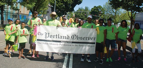 A large contingency march under the Portland Observer banner at Saturday's Good in the Hood parade.