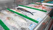 The market offers a variety of whole fish for sale, ready to be cleaned and cut to order.