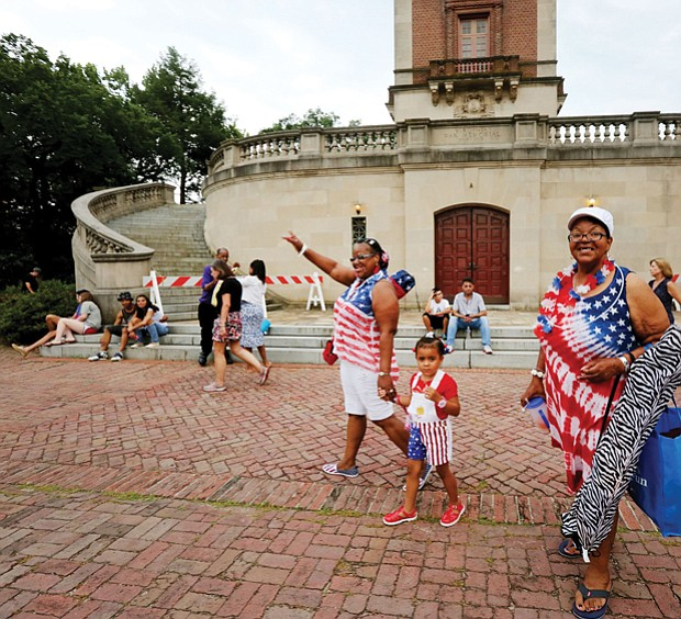 Wearing red, white and blue, Paulette Frye, left, leads her granddaughter, Maria Miles, 4, and her sister, Claudette Miles, to Dogwood Dell by the Carillon in Byrd Park, where hundreds of people on Tuesday spread blankets, put up lawn chairs and brought picnic baskets filled with goodies to enjoy music and entertainment before the annual fireworks display.
