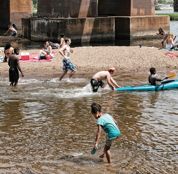 Area residents enjoy the cooling James River near Brown's Island on Monday,