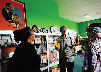 """H. Khalif Khalifah, center, speaks to visitors in the Nat Turner Library in his home during last Saturday's fundraising event, """"The Resurrection of Nat Turner: Save the Land."""""""