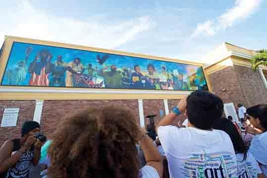 "In the summer of 2015, OneUnited Bank unveiled its revolutionary 550 square foot mural ""Thunder and Enlightening"" on the façade ..."