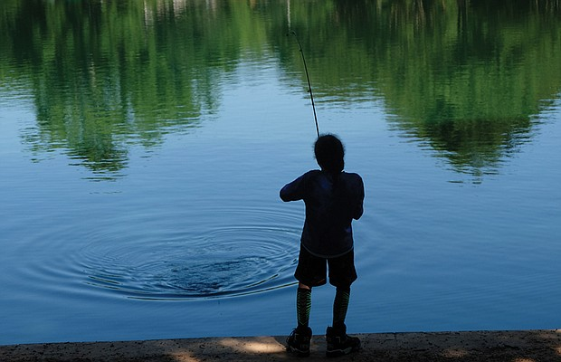 Gone fishin' Deican Jones works his rod and reel from the cool shade at Shields Lake in Byrd Park during a recent fishing expedition. In this instance, the fish that was nibbling at his line got away.