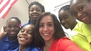 Teacher Kylie Cucalon poses with several students.