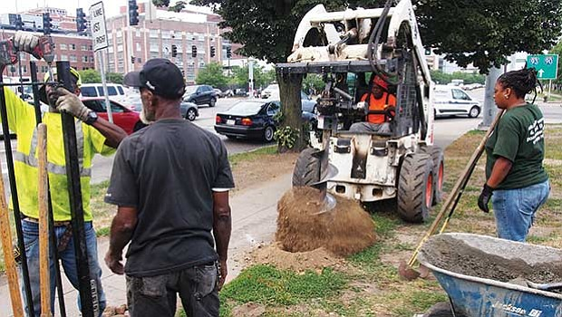 Working on a city job, McCoy Fence Co. workers drill post holes for a wrought iron fence along Melnea Cass Boulevard.