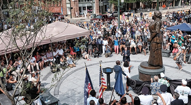 Cheers arise from the crowd of hundreds after the statue of Maggie L. Walker is unveiled at a ceremony last Saturday at the plaza at Broad and Adams streets.