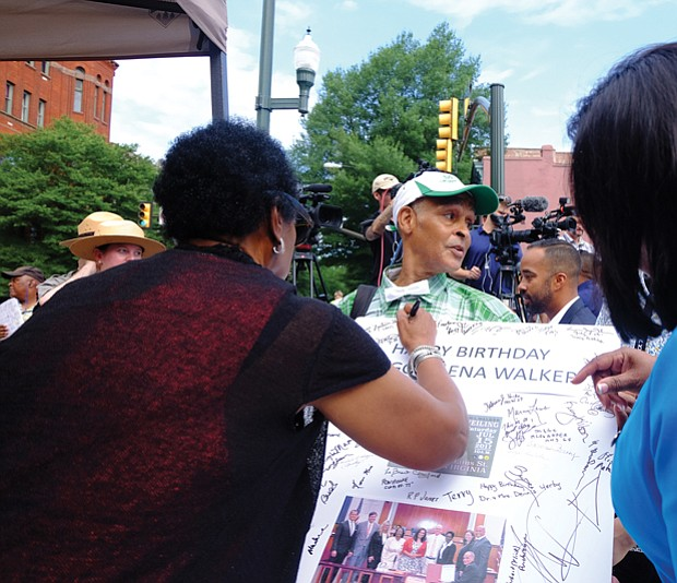 9. Melvin S. Jones Jr., a longtime advocate for the Walker statue, holds a giant birthday card honoring Mrs. Walker while Delegate Delores McQuinn, left, signs and Sen. Rosalyn Dance awaits the pen.