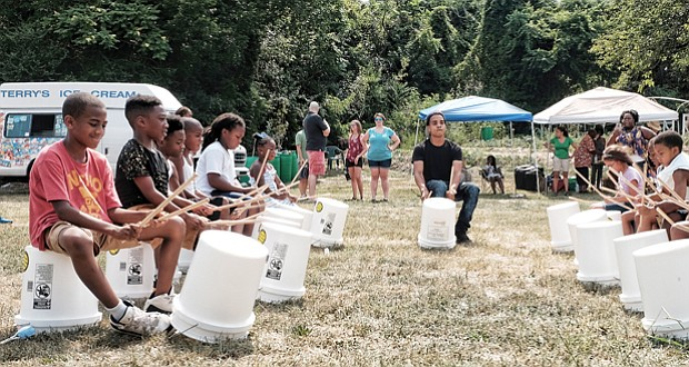 """Cultivating musical interest // Shyamuu Bhagat leads youngsters in a bucket drum workshop last Saturday at """"Drums in the Garden,"""" an event at the 5th District Mini Farm on Bainbridge Street in South Side to promote urban farming and healthy eating."""