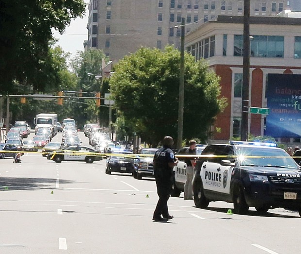 Cityscape // Crime tape and police and firefighters in action are all too common in Richmond and other cities. Above, officers and police cars pack the intersection of 3rd and Main streets in Downtown around 10:30 a.m. Tuesday following the police shooting of a man wielding a large knife and an ax. Police Chief Alfred Durham said officers shot the man when he did not respond to commands to drop the weapons, and a Taser proved ineffective in stopping him. When the man attacked the officers, two fired, hitting him. The man, later identified as Alexander J. Schoessel, 23, of Chesterfield, was pronounced dead at 10:31 a.m. Tuesday at a Richmond hospital. Officer John Rotondi also was hit by friendly fire during the incident. He was taken to a hospital, where he was treated and released. Right, firefighters hose down a smoldering pile of driftwood Tuesday afternoon underneath a pedestrian bridge across the James River that connects Brown's Island and Belle Isle in Downtown.
