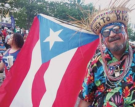 Edwin Rivera displays an abundance of Puerto Rican flags.