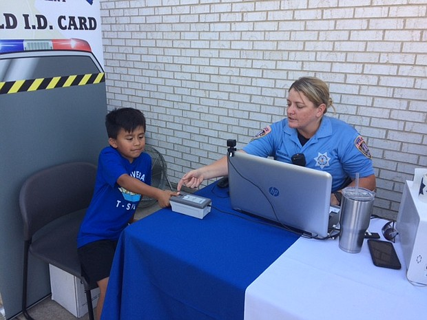 Mateo, 7, scans his fingerprint for an ID badge at the City of Joliet Police Department's National Night Out on Tuesday.