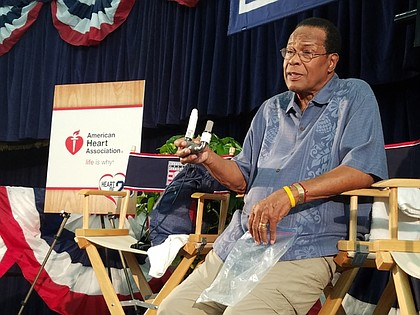 Carew holding his LVAD during a news conference.