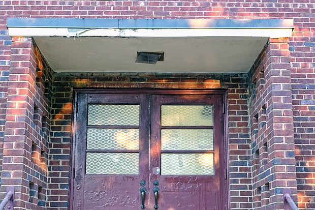 A weathered side entrance and light fixture at the school show some of the work that needs to be done.