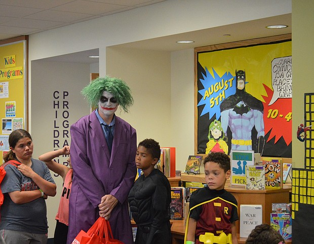 Batman's arch-nemesis The Joker waits in line for face painting at Comicopolis at the White Oak Library District's Lockport Branch on Saturday.