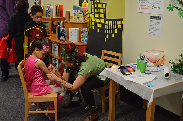 A young superheroine gets some design work done by a library volunteer at Comicopolis in Lockport.