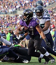 Baltimore Ravens running back Buck Allen (37) being chased by Seattle Seahawks defensive end Cliff Avril (56) in the game on December 13, 2015 at M&T Bank Stadium in Baltimore.