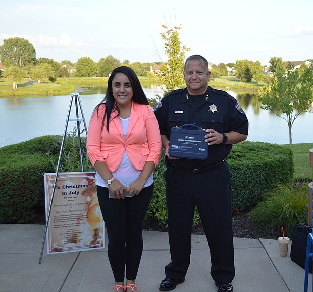 Will County Human Society shelter manager Sandra Lopez and Shorewood Police Chief Aaron Klima accept donations from Happy Tails, a group that holds fundraisers for animal welfare causes.