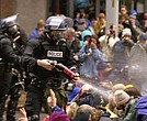 President Donald Trump seemed to endorse police brutality in a speech on Long Island, N.Y. This photo was taken during WTO protests in Seattle, November 30, 1999. Pepper spray is applied to the crowd. (Wikimedia Commons)