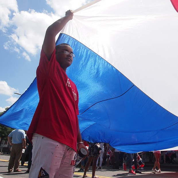 Emilio Echavarria holds up a corner of a large Dominican Flag.