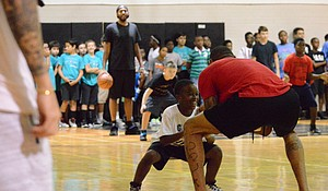 Kenyon Martin (in red shirt) teaches a child to navigate defense during his free basketball camp at the Becky Saner Recreation Center, July 28.