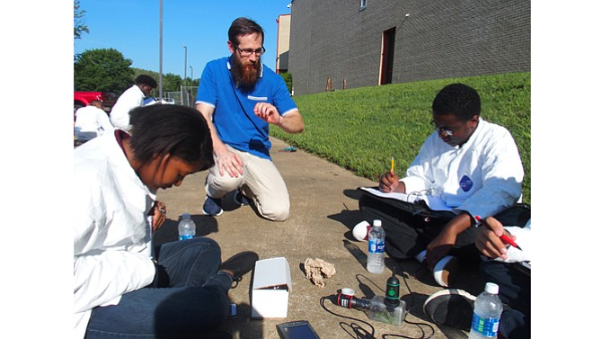 Craigmont High School teacher Wayne Oellig helps his students with a biology experiment related to the Aug. 21 solar eclipse.