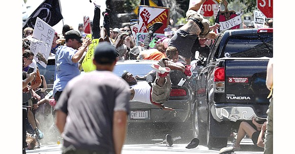 A car rammed into a crowd of protesters and a state police helicopter crashed into the woods Saturday as tension ...
