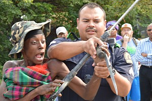 """Corporal B. Ledezma, with the Dallas Police Department, attempts to disarm the woman, who is later arrested without further incident, Aug. 2. The episode represents the hazardous situations described by Ibrahim Abdullah of the Beacon of Light Community Outreach Service Center as """"happening every day"""" in tent city."""