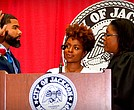 Chokwe Antar Lumumba (left) is sworn-in, becoming Jackson's youngest mayor. Court of Appeals Judge Latrice Westbrooks right) administers the oath of office to Lumumba as his wife Ebony looks on.