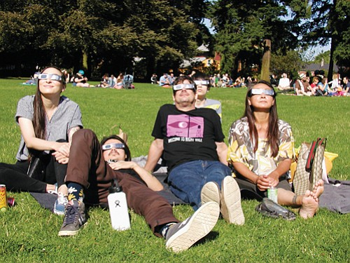 A group of visitors from Seattle gather on the lawn at Peninsula Park in north Portland Monday morning to view the Great Solar Eclipse.
