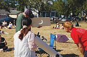 As a crowd of stargazers gather at Mount Tabor in southeast Portland to view the once-in-a-lifetime solar eclipse on Monday morning, a man who set up a telescope to project the image safely shows the sun being obscured by the moon as reflected on a piece of whiteboard paper.